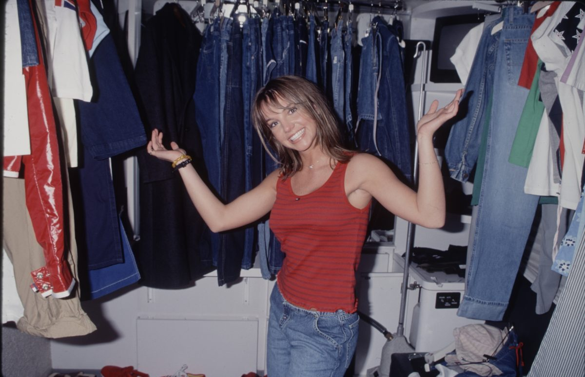 A young Britney Spears standing in a closet, smiling, with her hands up. She's wearing a red tank top and jeans.