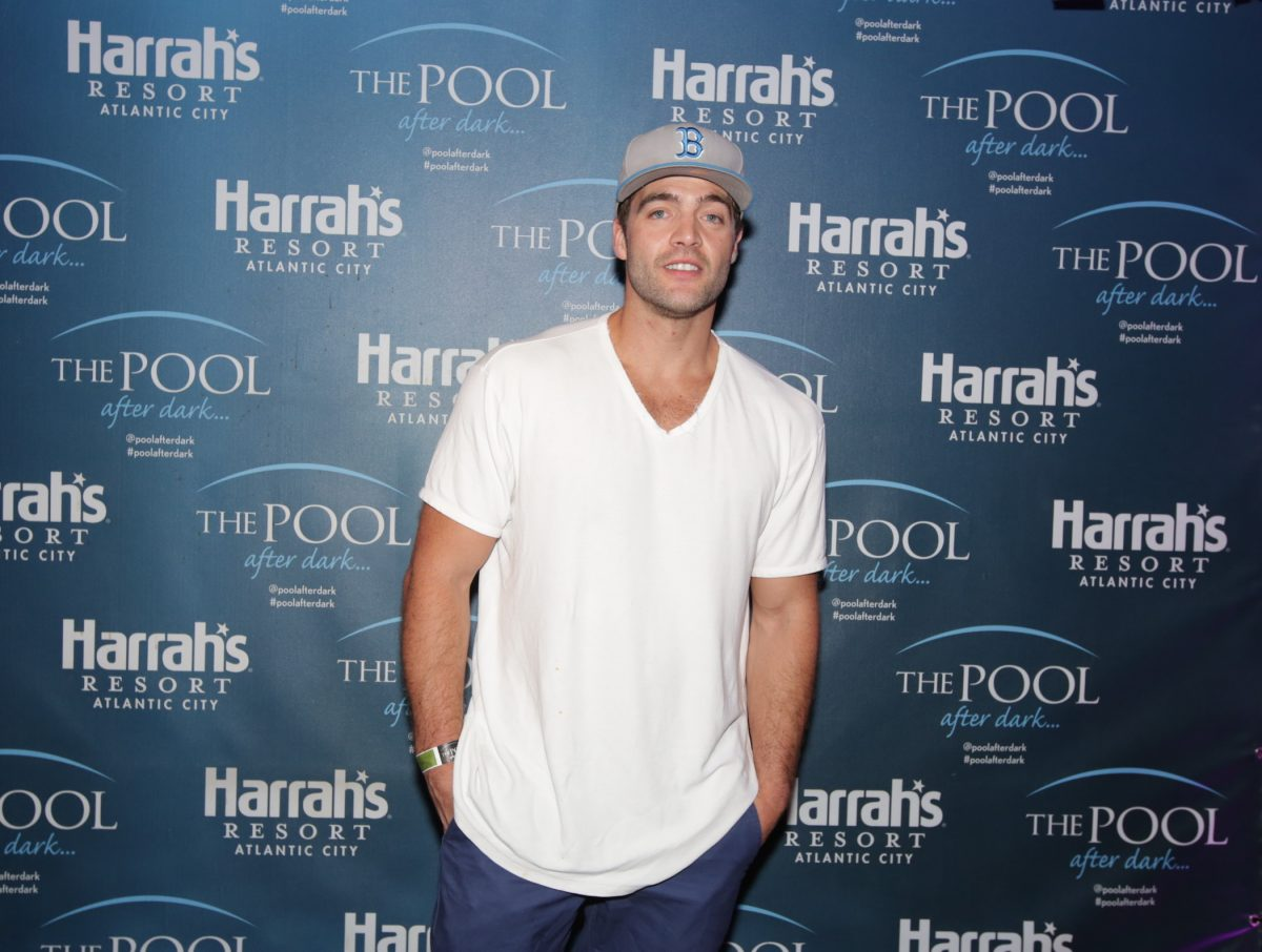 CT Tamburello from MTV's 'The Challenge' in a white T-shirt and a hat standing with hands in pockets for a camera