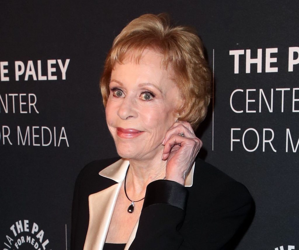 Carol Burnett smiles on red carpet and poses with her hand to her ear