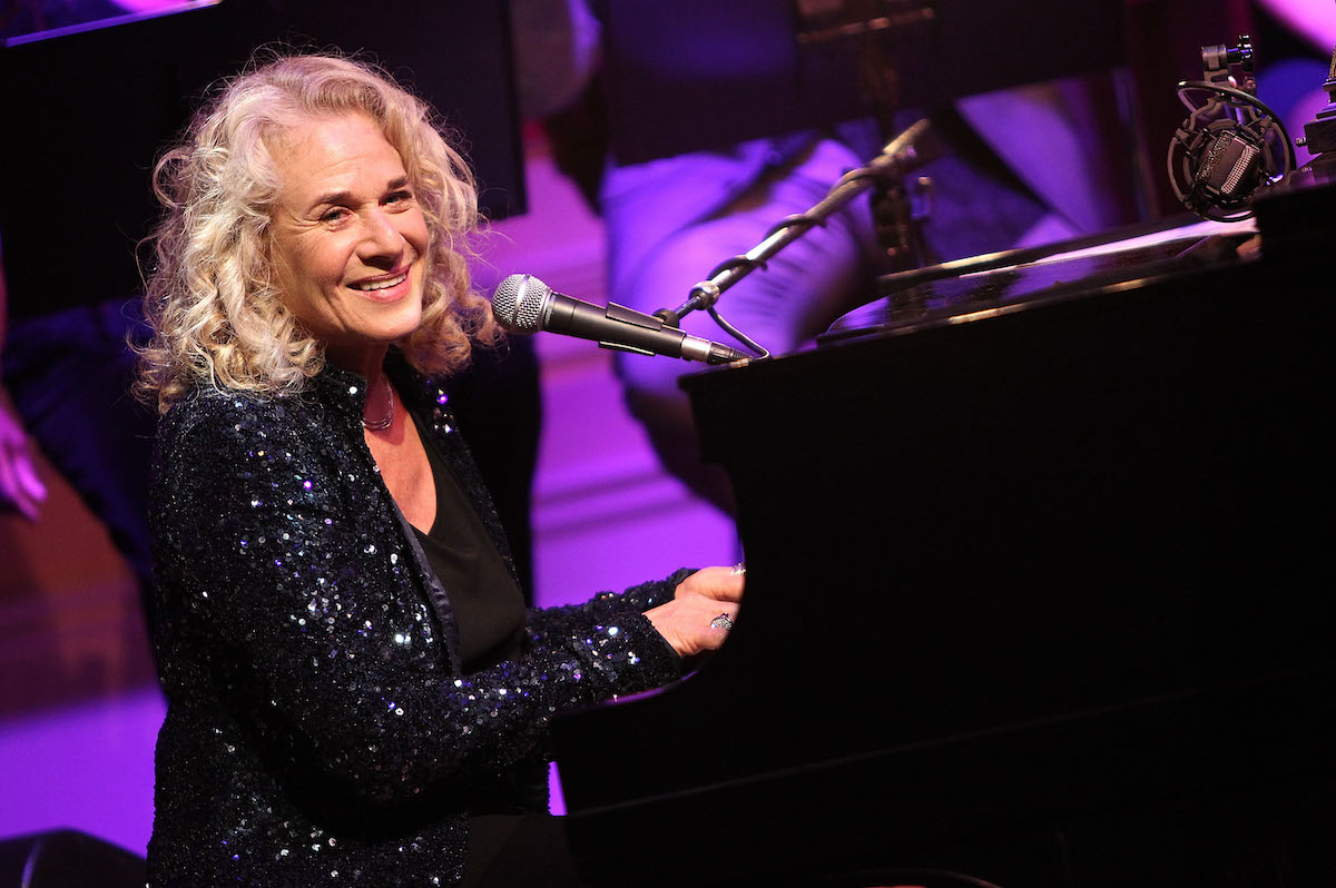 Carole King smiles as she sits at a piano and performs at the 2013 Library of Congress Gershwin Prize Tribute Concert