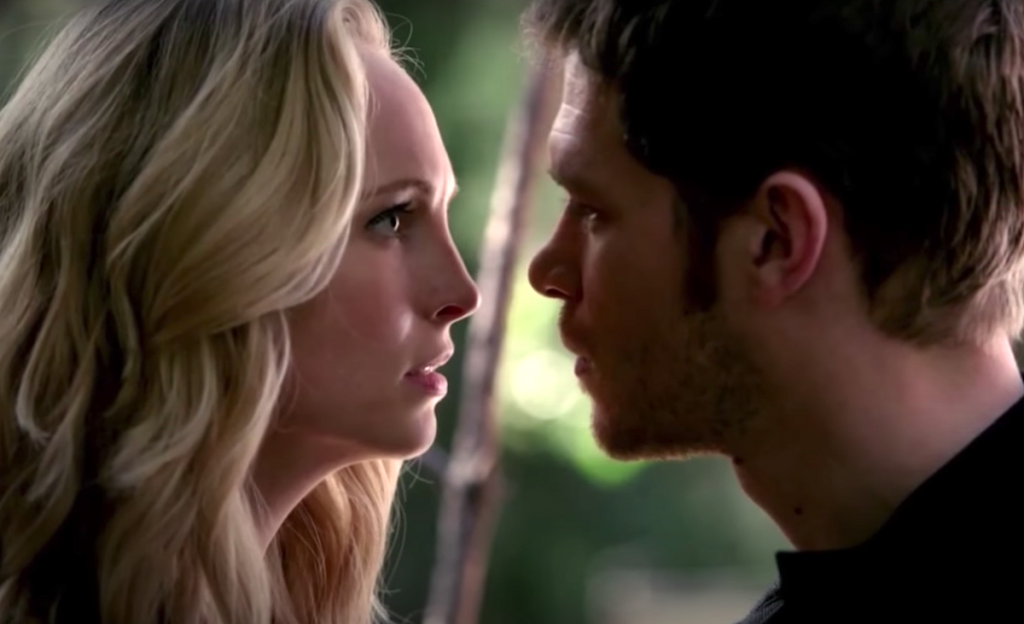 Candice King and Joseph Morgan stand face-to-face in the woods as Caroline and Klaus in 'The Vampire Diaries'