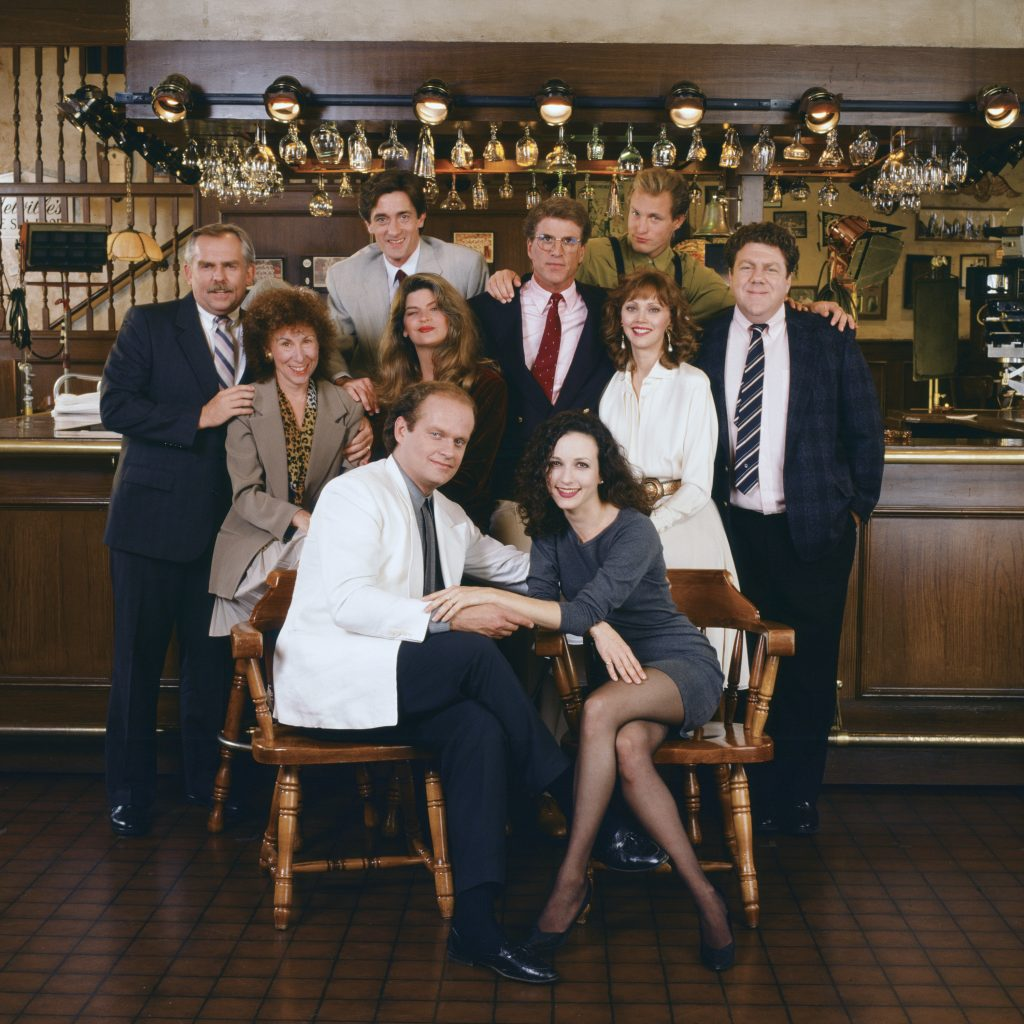John Ratzenberger as Cliff Clavin, Rhea Perlman as Carla LeBec, Roger Rees as Robin Colcord, Kirstie Alley as Rebecca Howe, Kelsey Grammer as Dr. Frasier Crane, Ted Danson as Sam Malone, Bebe Neuwirth as Dr. Lilith Sternin-Crane, Shelley Long as Diane Chambers, Woody Harrelson as Woody Boyd, and  George Wendt as Norm Peterson in a promotional photo for 'Cheers'