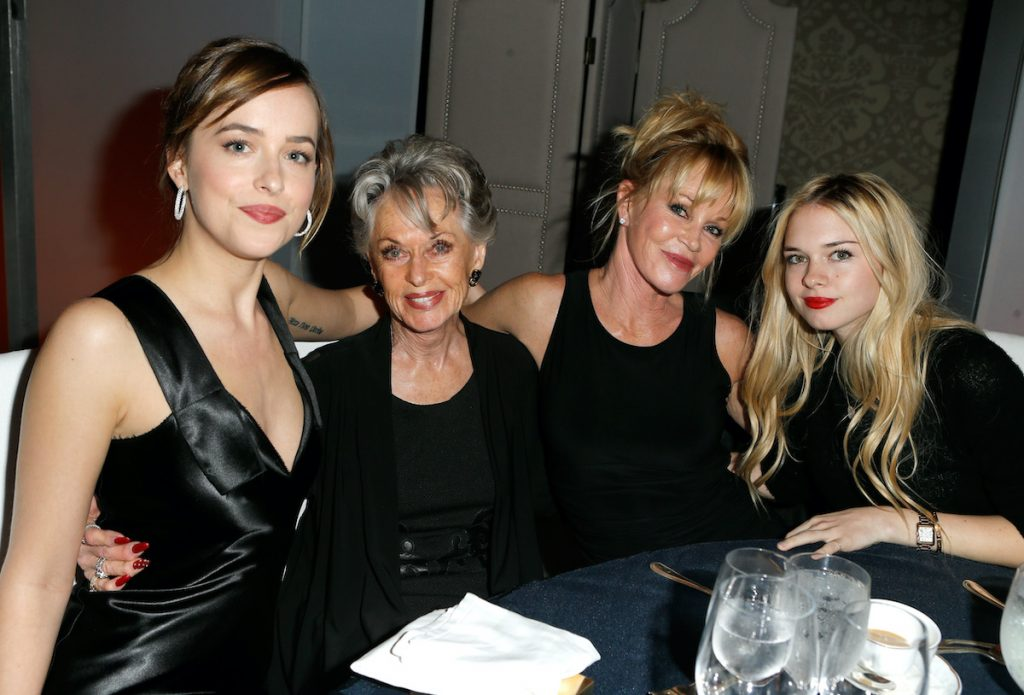 Dakota Johnson, Tippi Hedren, Melanie Griffith, and Stella Banderas sit at a table and pose for a photo at the 22nd Annual ELLE Women in Hollywood Awards on October 19, 2015