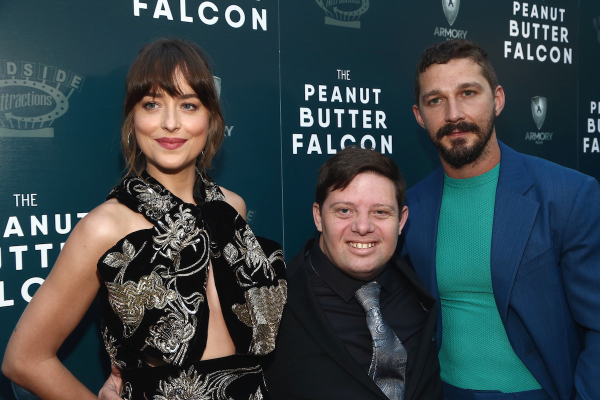 Dakota Johnson, Zack Gottsagen, and Shia LaBeouf pose for cameras together at a screening of 'The Peanut Butter Falcon'