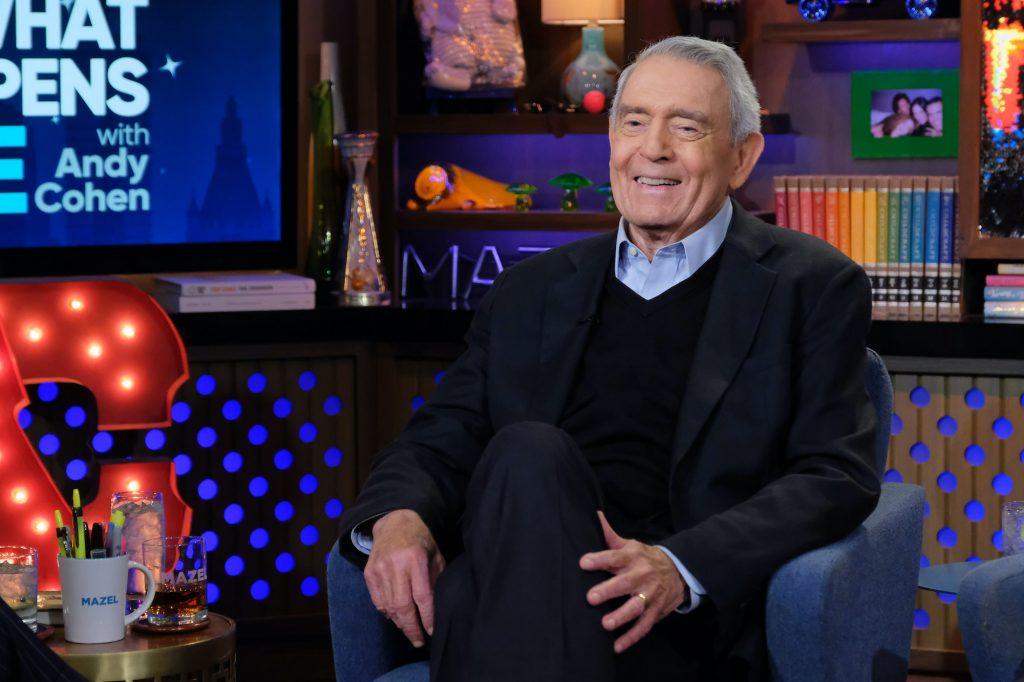Dan Rather smiling, seated in an armchair