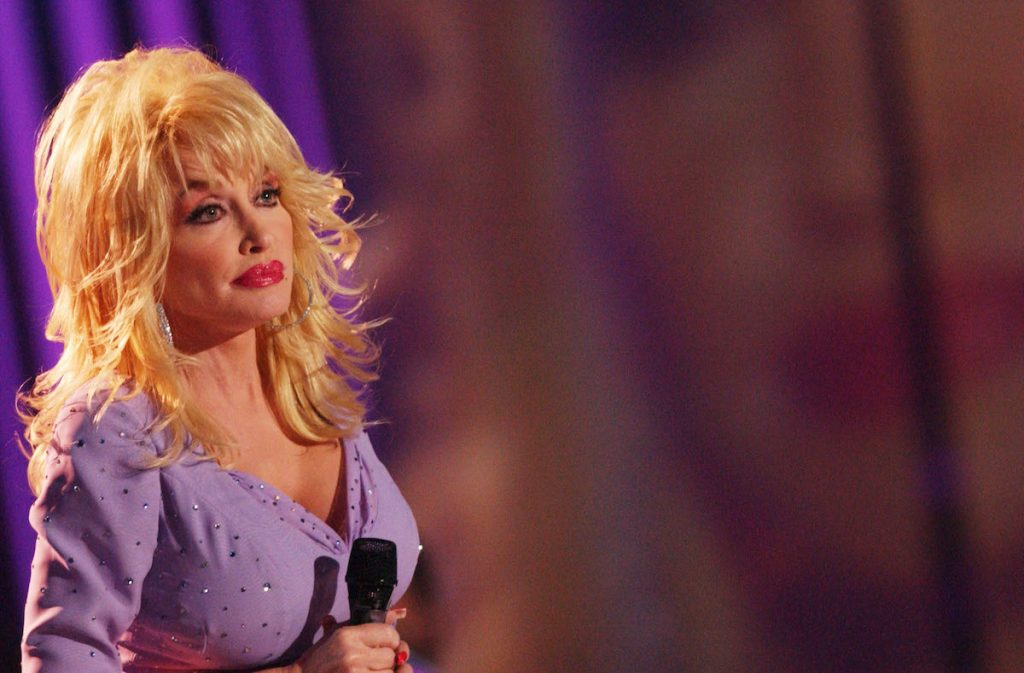Dolly Parton stands on stage looking serious holding a microphone on CMT 100 GREATEST LOVE SONGS
