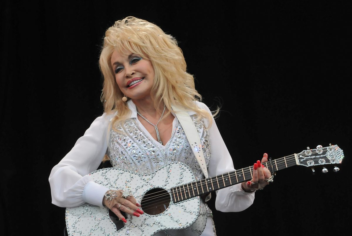 Dolly Parton in a white, sparkly shirt playing a white, sparkly guitar on stage.