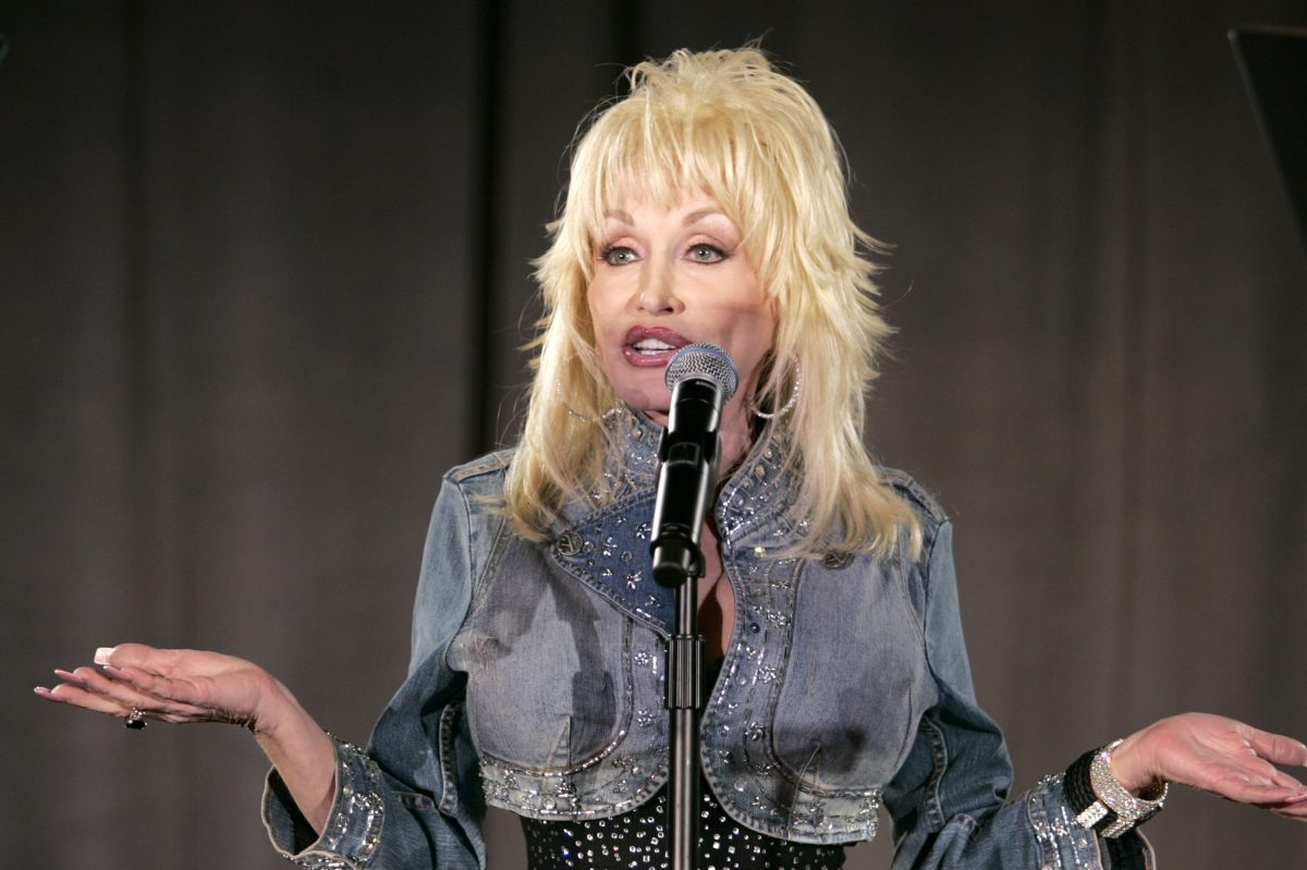 Dolly Parton during 2006 Weinstein Company Pre-Oscar Party. She's in a jean jacket, singing into a microphone.