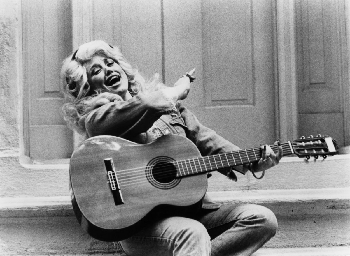 Dolly Parton spiritedly plays the guitar in black and white in 1970. She's wearing her hair big and curl and a jean outfit.