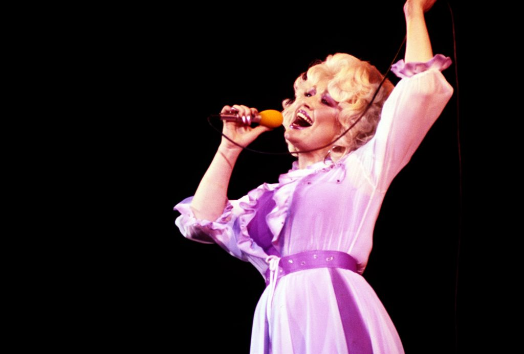 Dolly Parton singing on stage in a lavender dress.