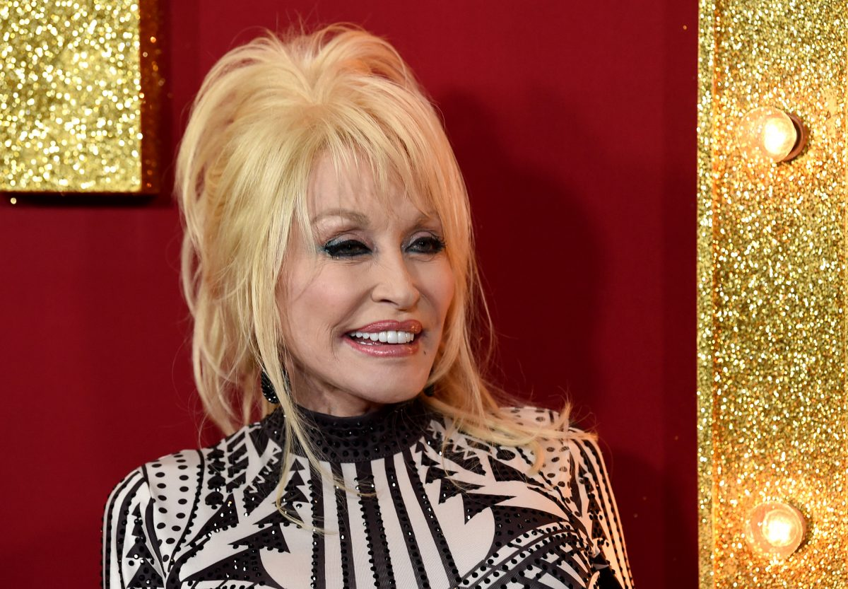 Dolly Parton at the premiere of 'Dumplin'' on the red carpet. She's in a black and white top and looking to the left of the camera, smiling.