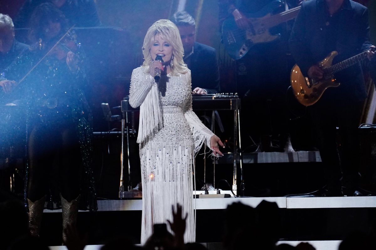 Dolly Parton performing on stage. She's in a white fringe dress.