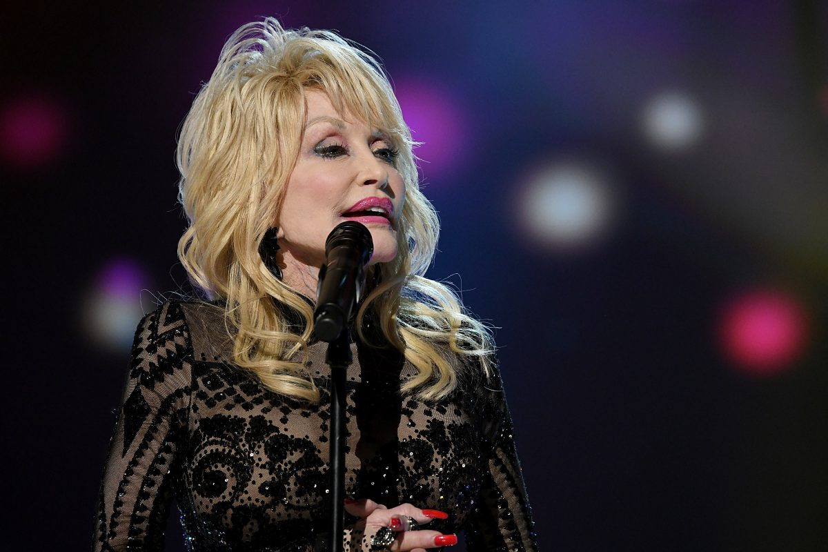 Dolly Parton performs on stage in Los Angeles, CA in 2019. She's wearing a black outfit.