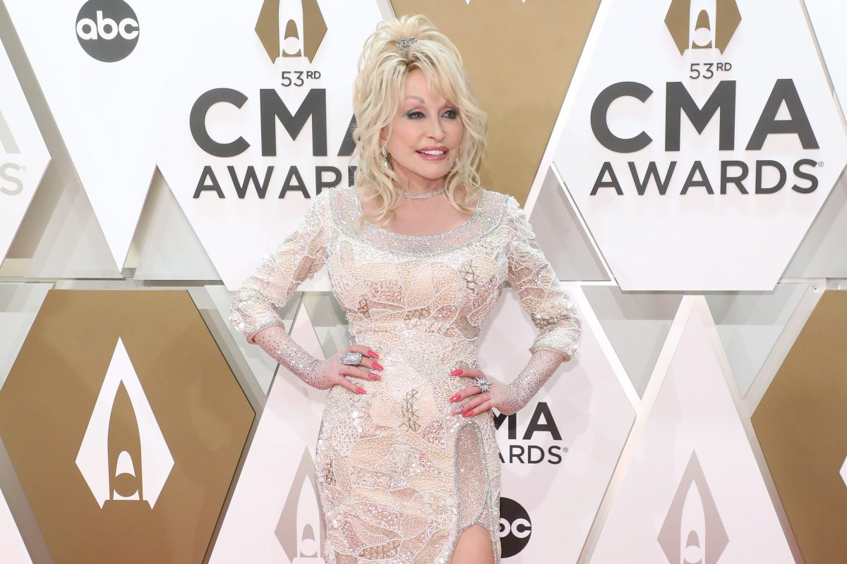 Dolly Parton posing on the CMAs red carpet. She's in a white dress with rhinestones. She's posing with her hands on her hips.