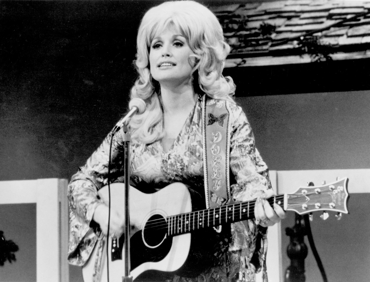 Black and white photo of Dolly Parton performing on guitar in 1974