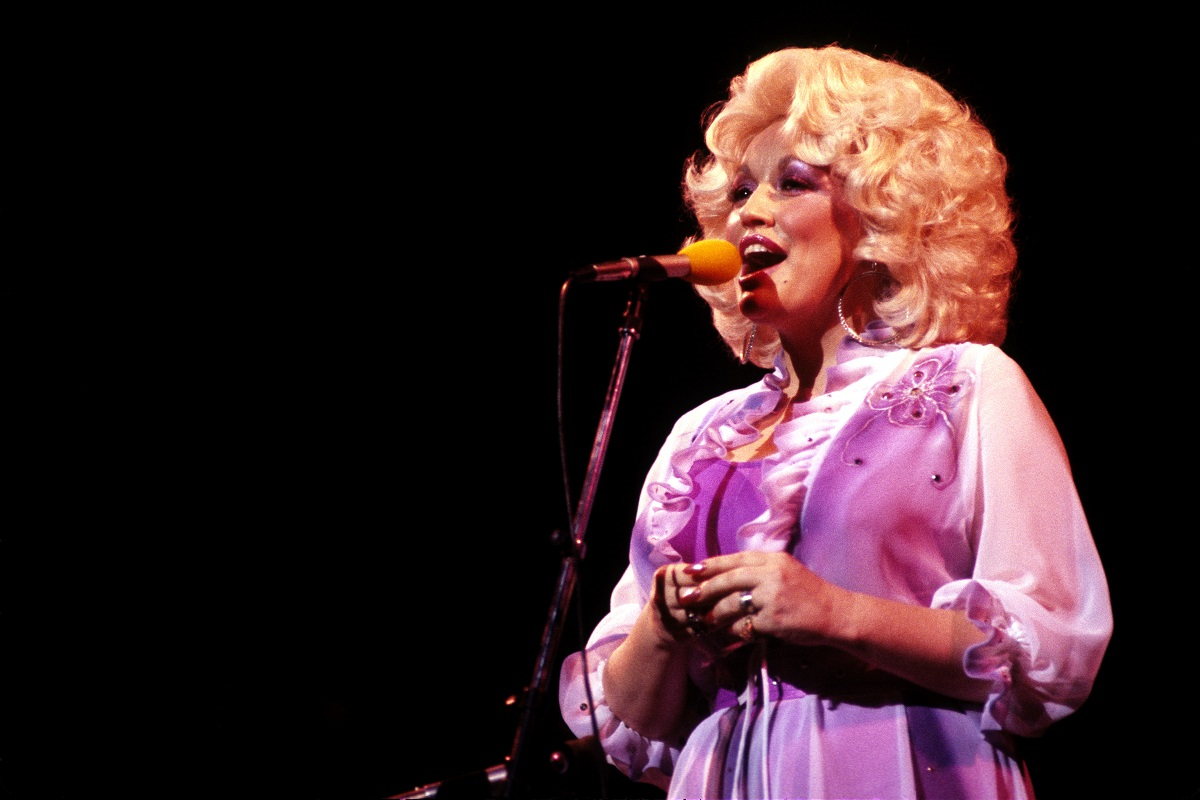 Dolly Parton in a pink dress singing at a microphone