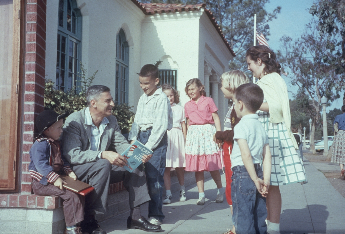 Dr. Seuss (Theodor Seuss Geisel, 1904 - 1991) sits outdoors talking with a group of children, holding a copy of his book, 'The Cat in the Hat', La Jolla, California, April 25, 1957