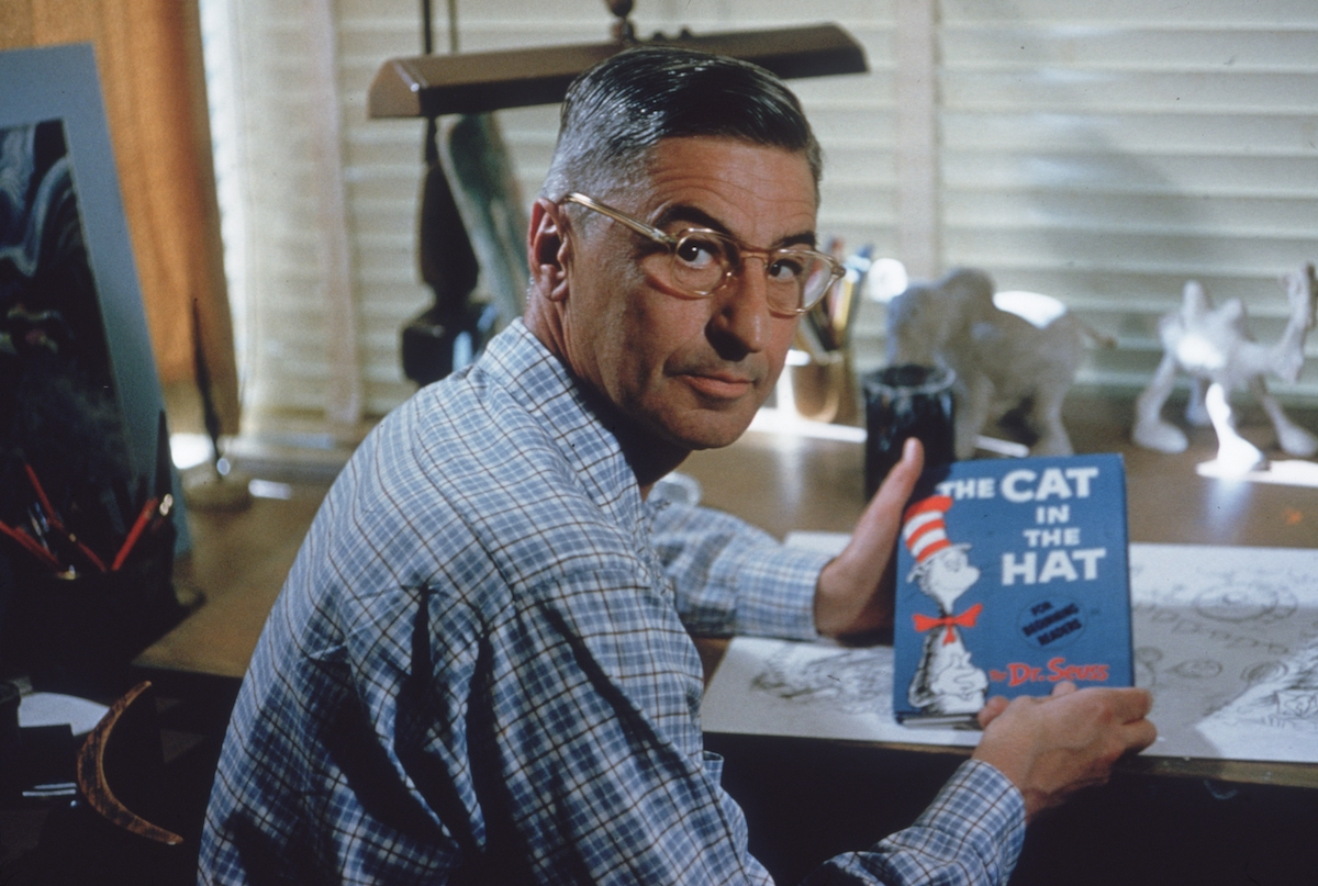 Dr. Seuss sits at his drafting table in his home office with a copy of his book The Cat in the Hat. | Gene Lester/Getty Images