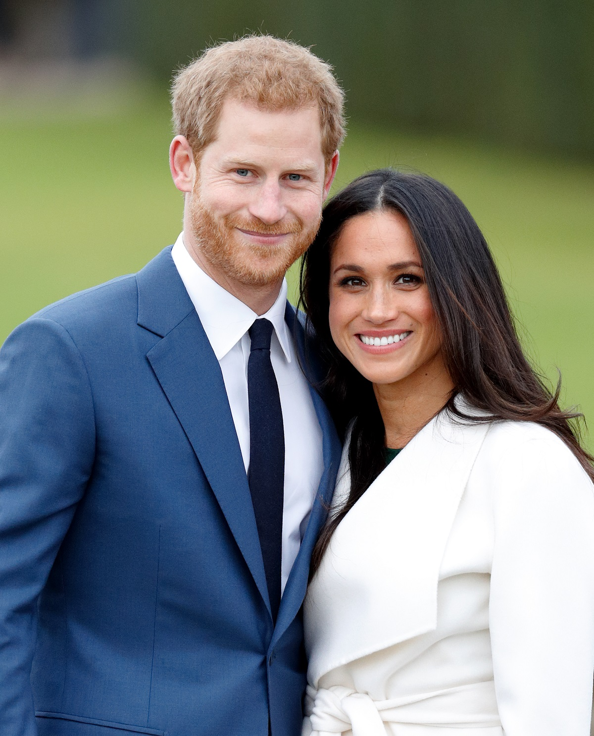 Prince Harry and Meghan Markle smiling at an official photocall to announce their engagement at The Sunken Gardens, Kensington Palace on November 27, 2017 in London, England
