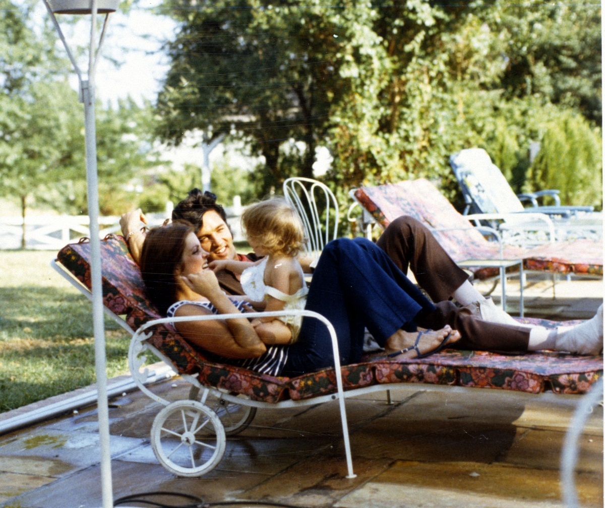 Priscilla and Elvis Presley lying on a lawn chair in Hawaii with Lisa Marie on Priscilla's lap