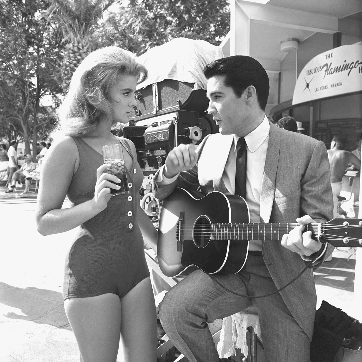 Ann-Margret in a bathing suit and Elvis Presley in a suit playing the guitar as their characters in 'Viva Las Vegas'