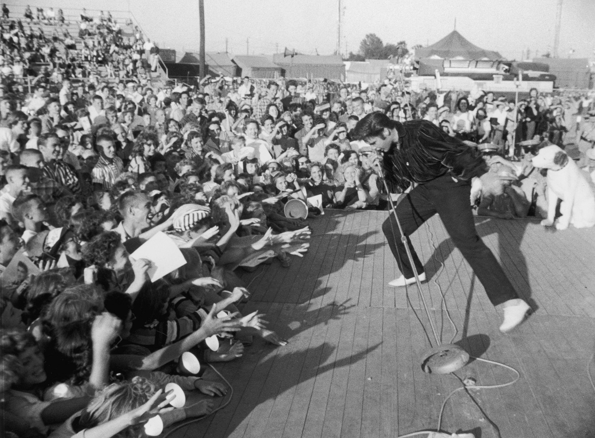 Elvis Presley performing in front of a crowd in 1957