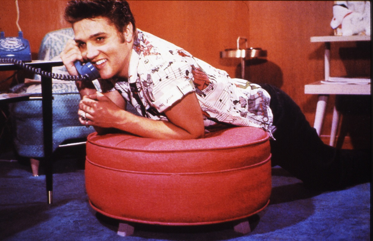 Elvis Presley in a posed color photo, leaning on a stool as he talks on the phone