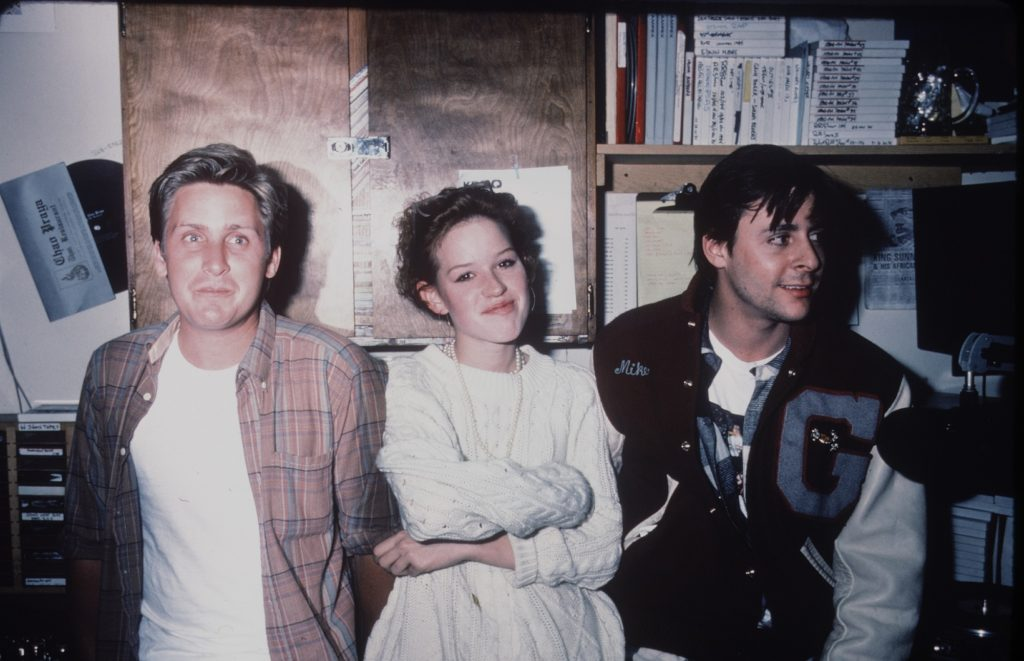 Actors Emilio Estevez, Molly Ringwald, and Judd Nelson smile in a candid photo together