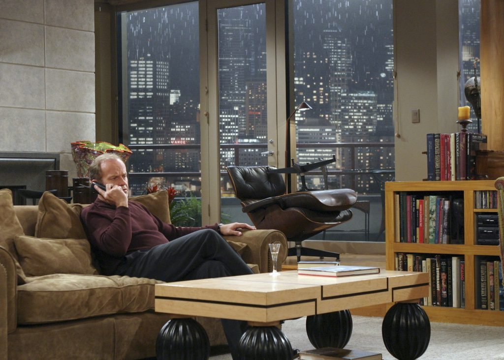 Kelsey Grammer as Dr. Frasier Crane sitting on a couch in front of a cityscape