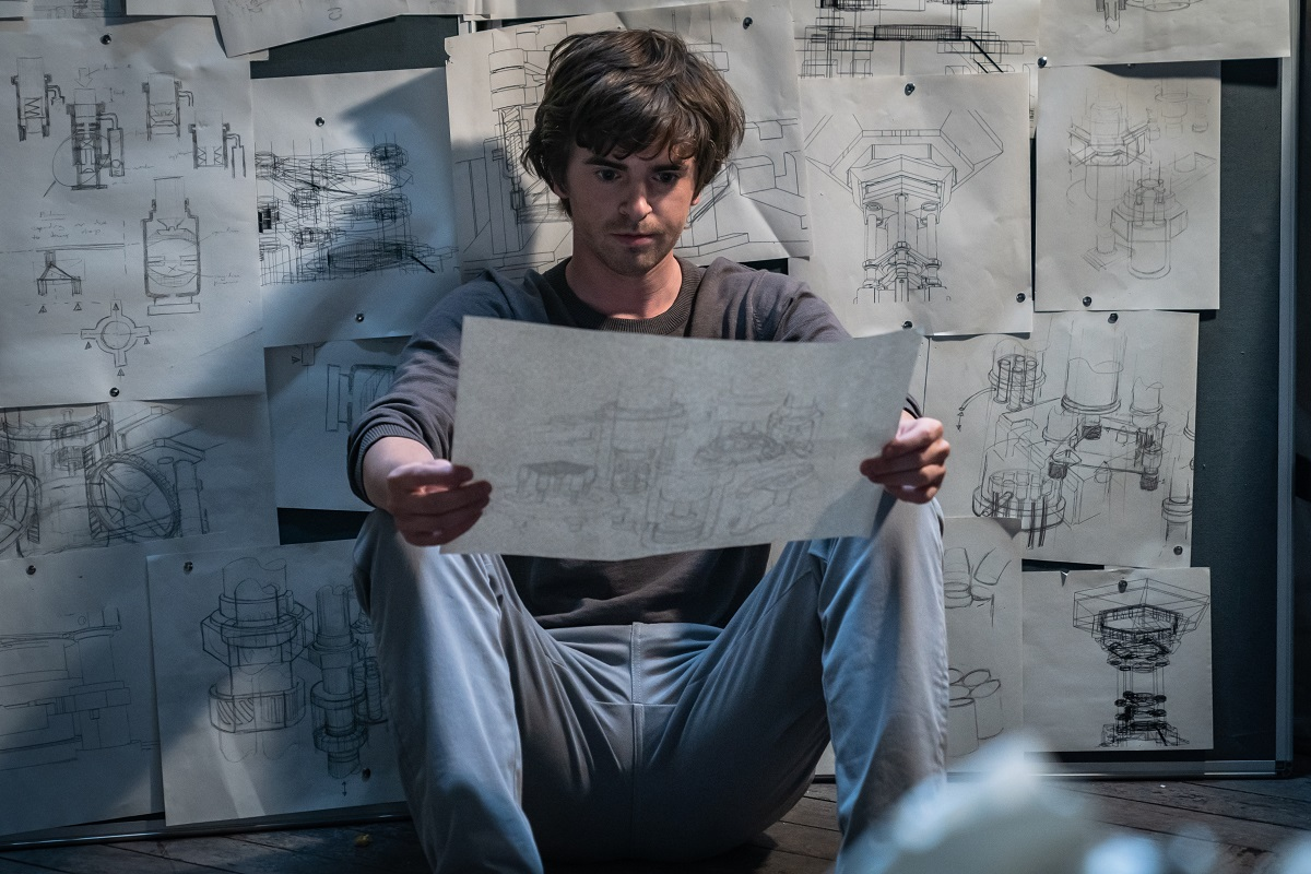 Freddie Highmore examining blueprints in a still from 'The Vault'