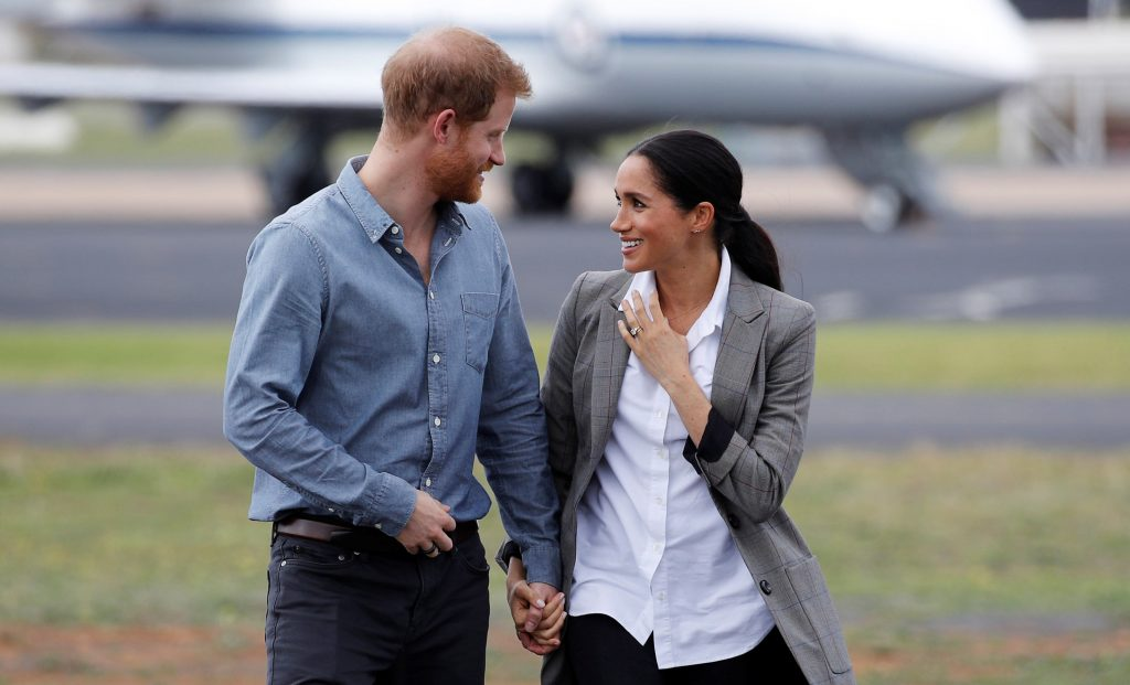 Prince Harry and Meghan Markle holding hands and smiling at each other as they arrive at Dubbo Airport