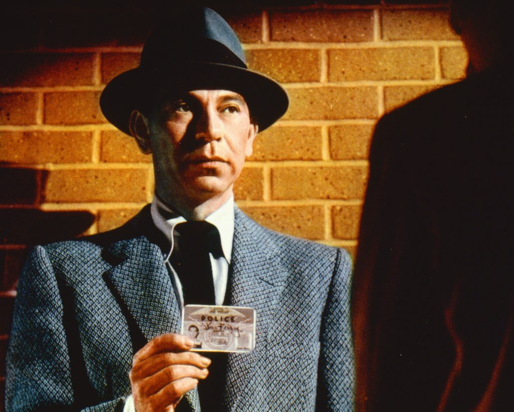 Actor Jack Webb poses as Sergeant Joe Friday wearing a grey jacket and a grey fedora, with a black band, while holding up his warrant card in a publicity still issued for the US television series, 'Dragnet', 1955