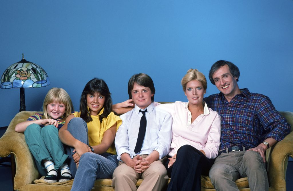 The cast of 'Family Ties' sits together on a couch in 1982: (L to R): Tina Yothers as Jennifer Keaton, Justine Bateman as Mallory Keaton, Michael J. Fox as Alex P. Keaton, Meredith Baxter as Elyse Keaton, and Michael Gross as Steven Keaton