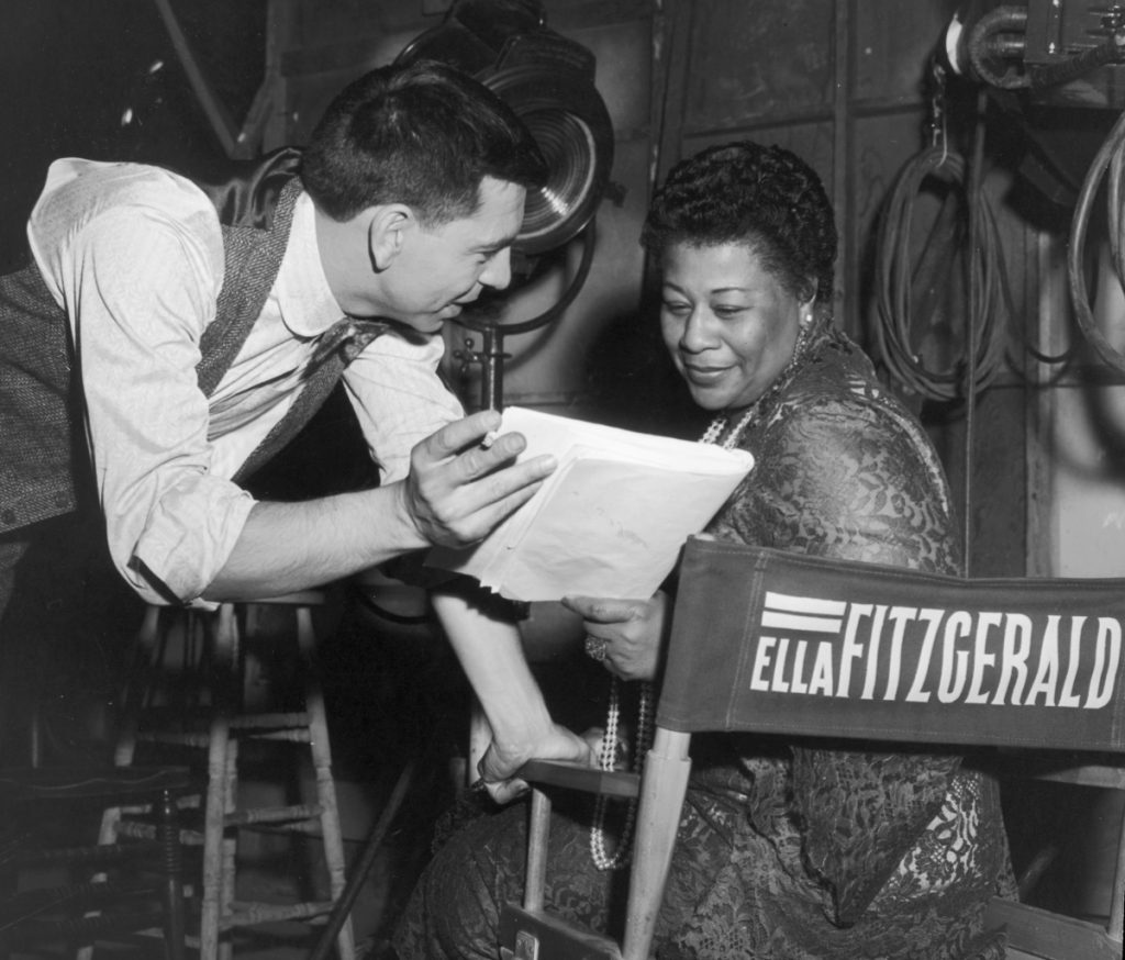 American actor and director Jack Webb discusses a script with American jazz singer Ella Fitzgerald behind the scenes, possibly on the set of Webb's film, 'Pete Kelly's Blues,' in which Fitzgerald had a role, 1955