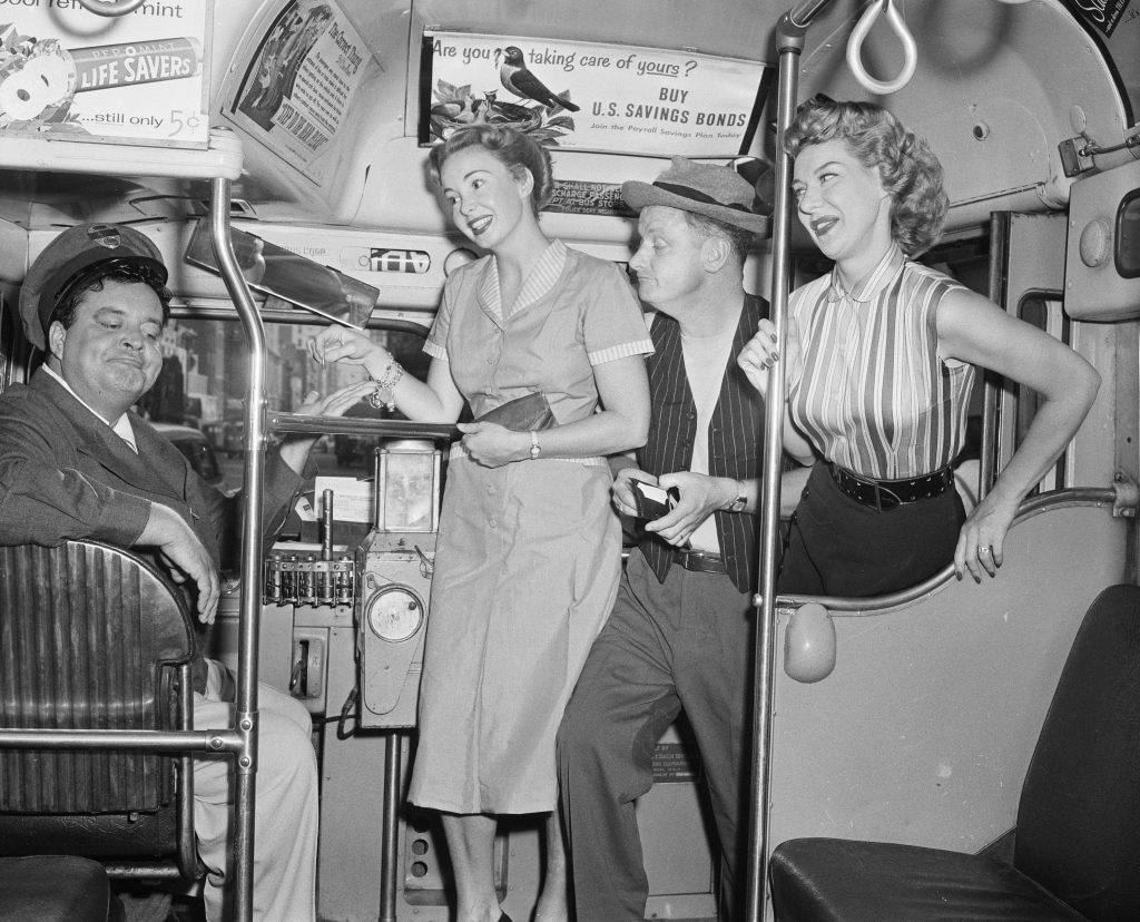 The cast of 'The Honeymooners' aboard a bus in 1955: Jackie Gleason as Ralph Kramden is in the driver's seat, while Audrey Meadows as Alice Kramden, Art Carney as Ed Norton and Joyce Randolph as Trixie Norton climb aboard
