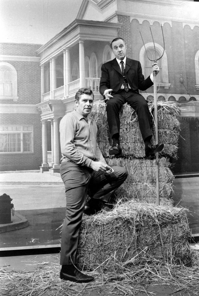 Andy Griffith (left) with his manager Dick Linke in 1969. The two pose on a stack of hay bales.