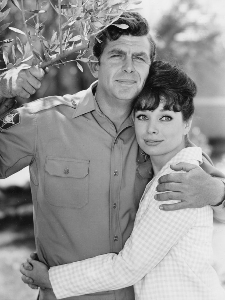 Andy Griffith and Aneta Corsaut stand next to a tree in an embrace, 1964