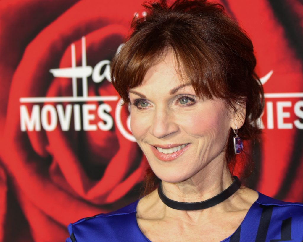 Actor Marilu Henner attends a Hallmark Channel and Hallmark Movies and Mysteries event in 2017. She wears a black choker and blue blouse with her red hair in a bun.