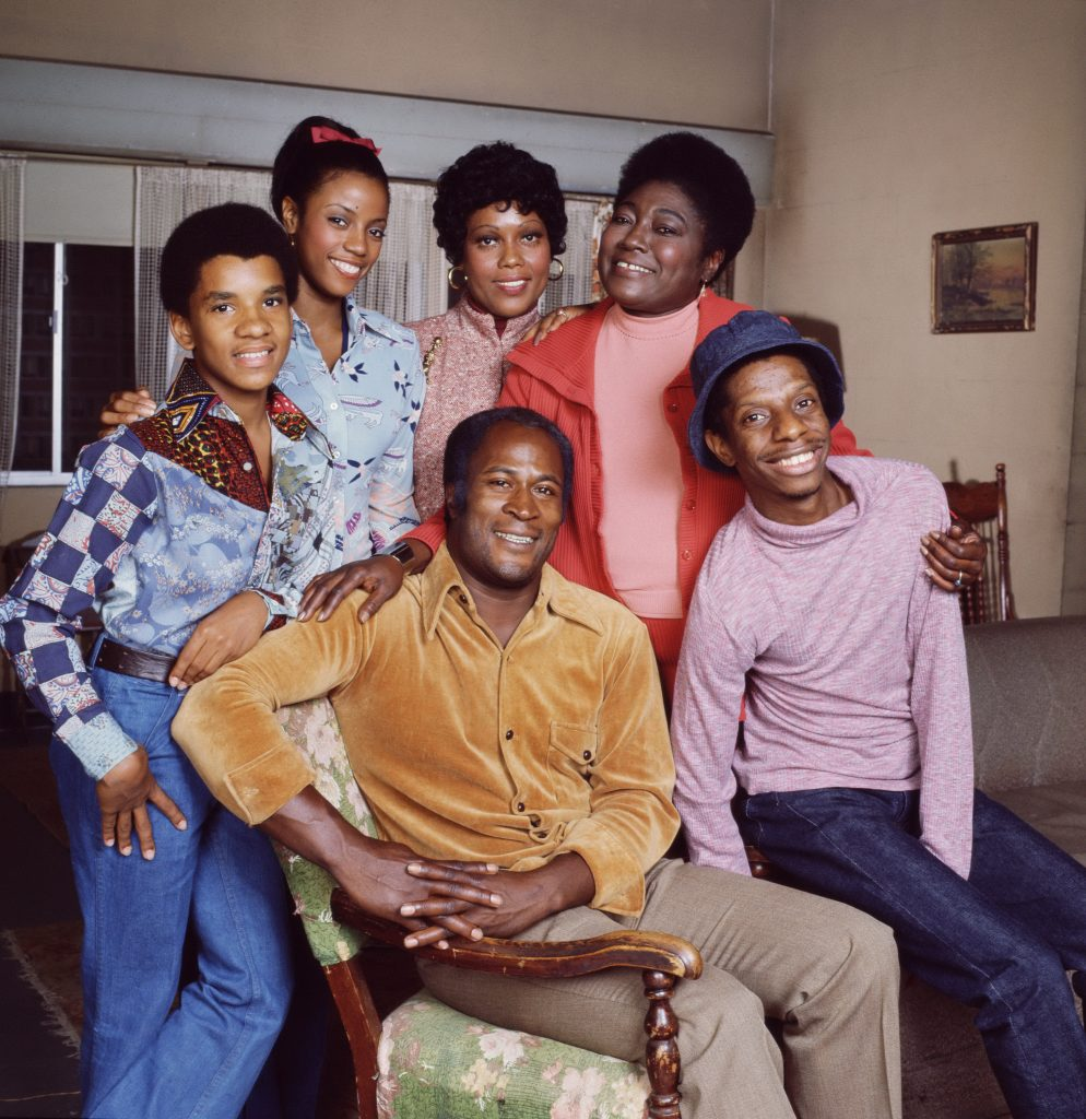 A portrait of the cast of 'Good Times': Pictured are, front row, American actors John Amos as James Evans (left) and Jimmie Walker as J.J. Evans; back row, from left, Ralph Carter as Michael Evans, Bern Nadette Stanis as Thelma Evans, Ja'net DuBois as neighbor Willona Woods, and Esther Rolle as Florida Evans