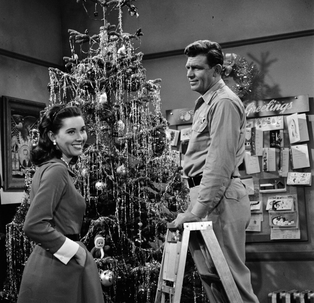 (L to R): Actor Elinor Donahue as Ellie Walker and Andy Griffith as Sheriff Andy Taylor decorate a Christmas tree in a scene from 'The Andy Griffith Show'