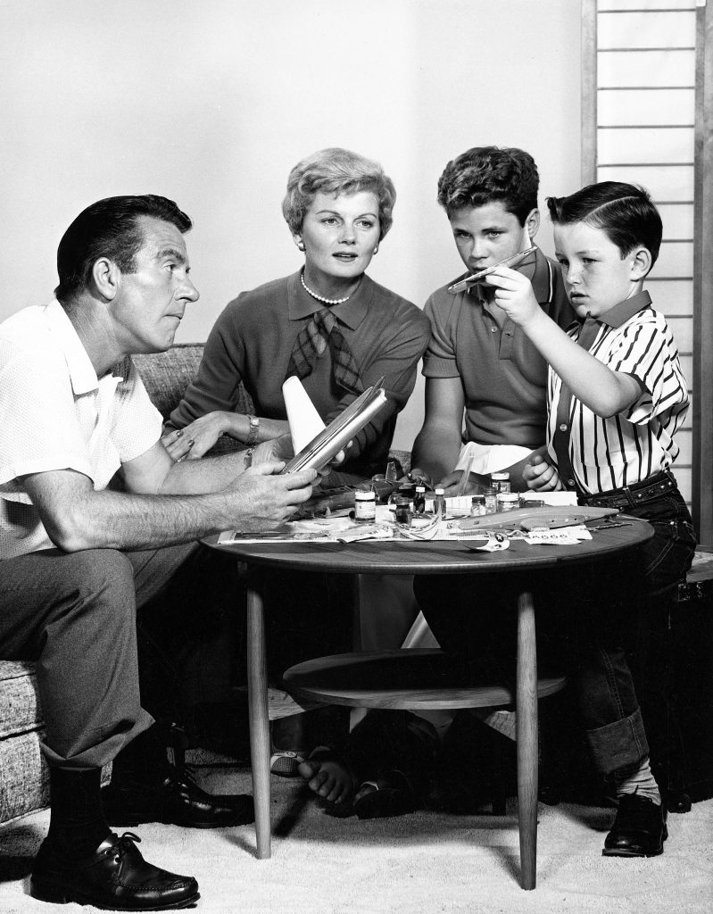 The cast of 'Leave It to Beaver' sit together as the Cleaver boys assemble a model airplane: (L to R): Hugh Beaumont, Barbara Billingsley, Tony Dow, and Jerry Mathers
