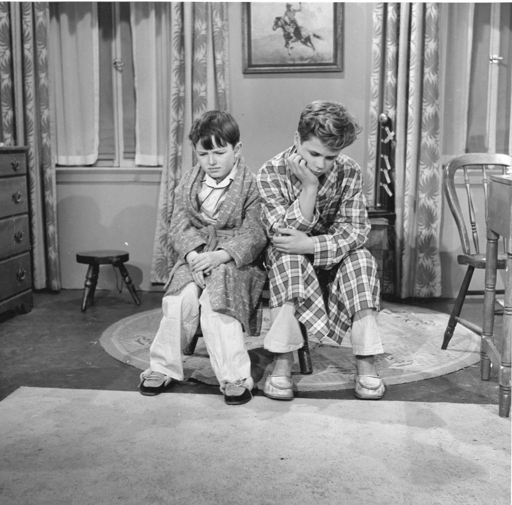 (L to R): Jerry Mathers as Beaver Cleaver and Tony Dow as Wally Cleaver are dressed in robes and sitting forlornly in a scene from 'Leave It to Beaver'