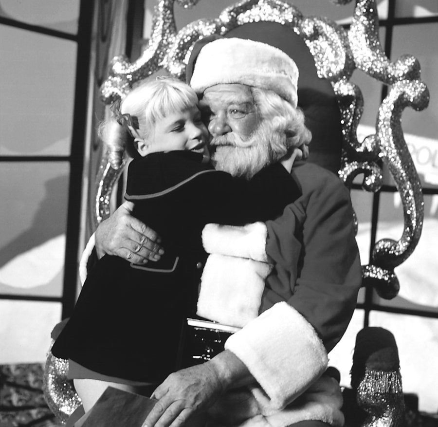 Susan Olsen as Cindy Brady sits on the lap of Hal Smith as Santa Claus in an episode of 'The Brady Bunch,' 1969