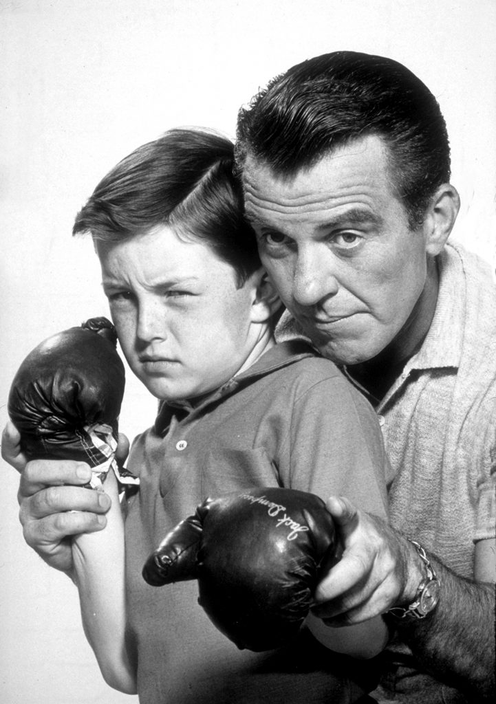 Hugh Beaumont, right, gives Jerry Mathers a boxing lesson in a scene from 'Leave It to Beaver,' 1959