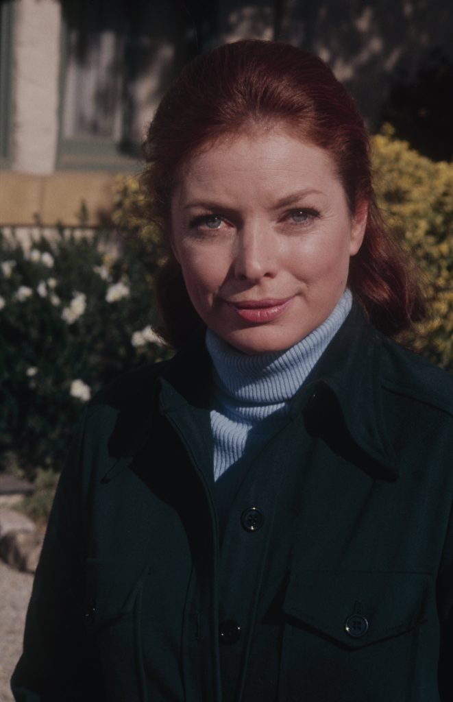 Actor Aneta Corsaut poses for a photo in a blue turtleneck, dark jacket, and her red hair pulled back, 1973
