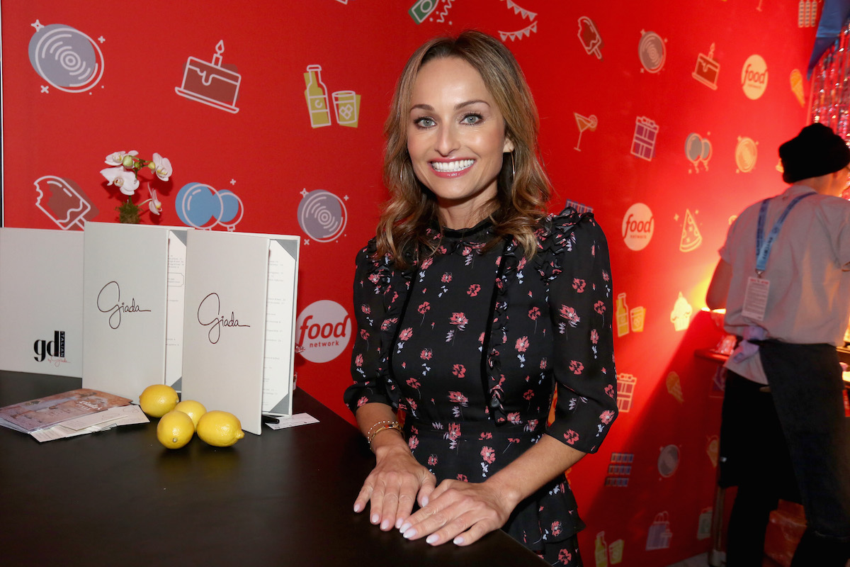 Giada De Laurentiis smiles as she stands at a table while attending Food Network's 25th Birthday Party during the 2018 New York City Wine & Food Festival