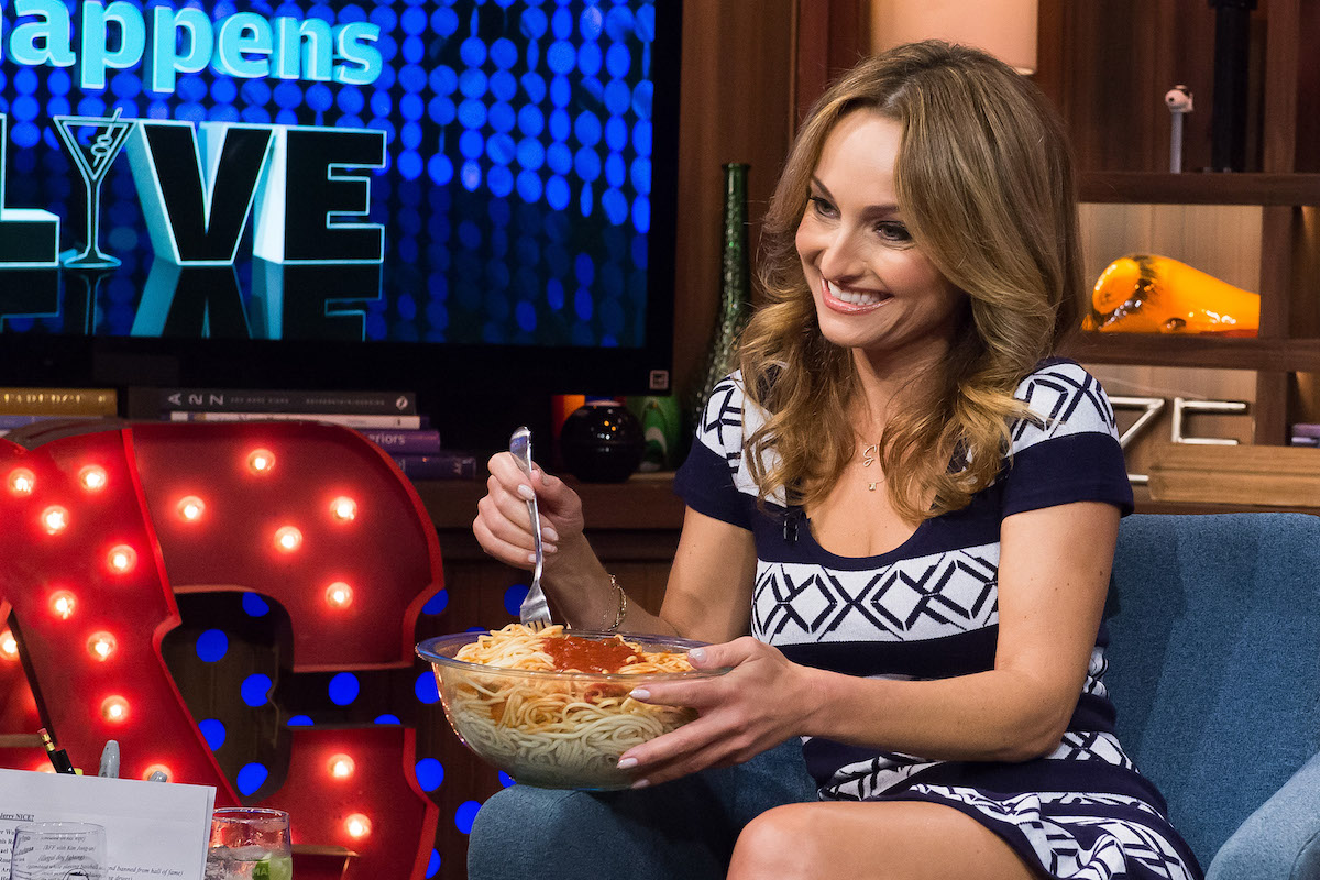 Giada De Laurentiis eats spaghetti as she smiles and sits on a couch during 'Watch What Happens Live with Andy Cohen'