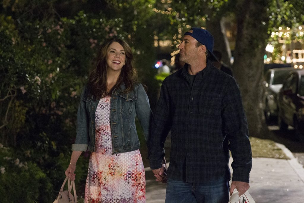 Lauren Graham as Lorelai Gilmore and Scott Patterson as Luke Danes walk down a street in Stars Hollow in 'Gilmore Girls: A Year in the Life'