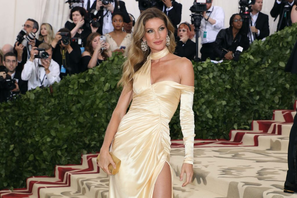 Gisele Bündchen smiling in front of a blurred crowd