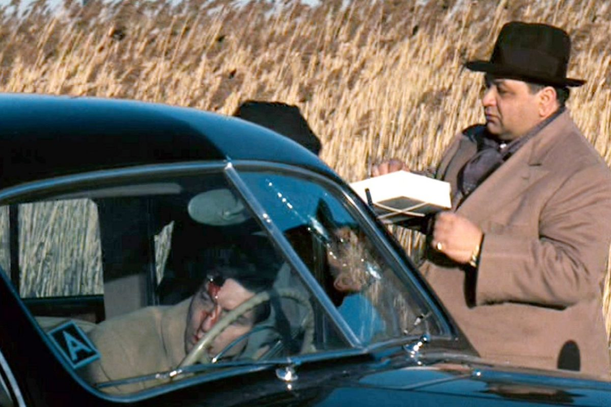 Richard Castellano stands next to a car holding a box of cannoli during a scene from 'The Godfather.' The car's driver is bloody and dead